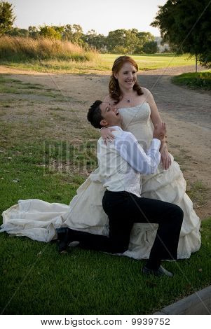 just married couple kneeling smiling and playing outside