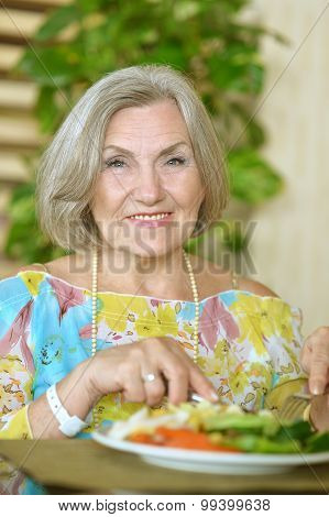 Senior woman eating breakfast