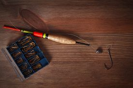 picture of fishing bobber  - Fishing tools hook and bobber on a wooden background - JPG