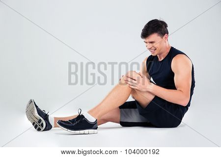 Portrait of a fitness man suffering from pain in a knee isolated on a white background