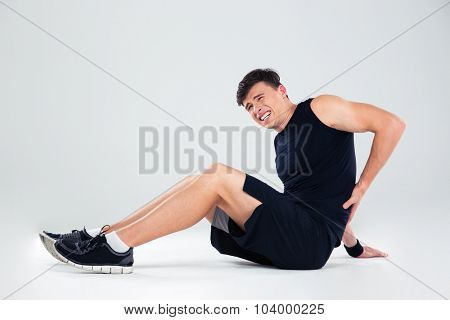 Portrait of a fitness man having back pain isolated on a white background