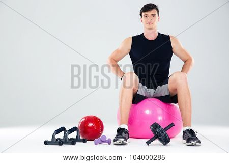 Portrait of a fitness man sitting on the ball isolated on a white background
