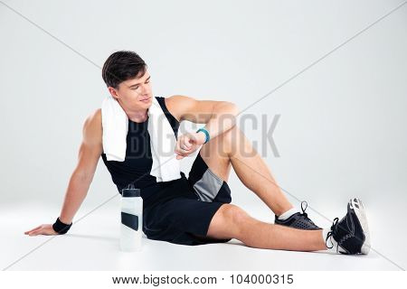 Portrait of a happy athletic man resting on the floor and looking on fitness tracker isolated on a white background