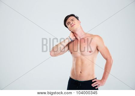 Portrait of a handsome man having neck pain isolated on a white background