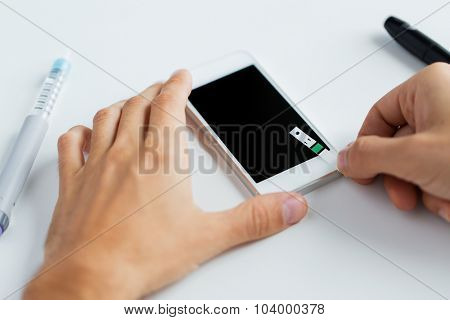 medicine, diabetes, glycemia, health care and people concept - close up of man with smartphone checking blood sugar level by glucometer at home