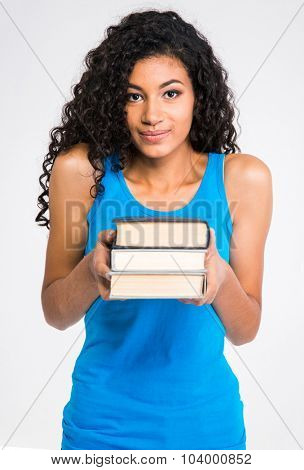 Portrait of a beautiful afro american woman holding books isolated on a white background