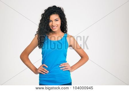 Portrait of a smiling afro american woman standing isolated on a white background and looking at camera