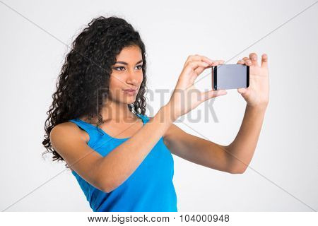 Portrait of a pretty afro american woman making selfie photo isolated on a white background