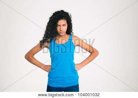 Portrait of angry afro american woman standing isolated on a white background and looking at camera