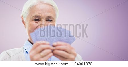 age, game, gamble, poker and people concept - close up of happy smiling senior woman playing cards over violet background