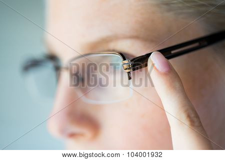business, vision and people concept - close up of woman in eyeglasses pointing finger to earpiece