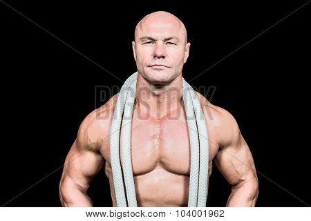 Portrait of confident fit man with rope around neck against black background