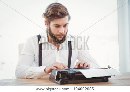 Hipster working on typewriter at desk in office