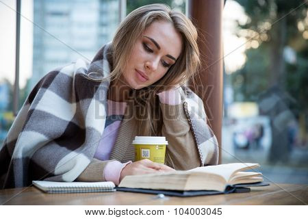 Portrait of a charming girl reading book in cafe