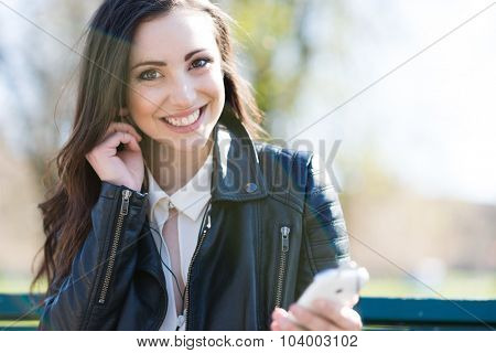 Portrait of a smiling young woman using earphones attached to a mobile phone. Some controlled flare in the foreground to give a more dynamic look