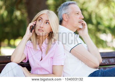 Senior couple sitting back to back talking on mobile phones