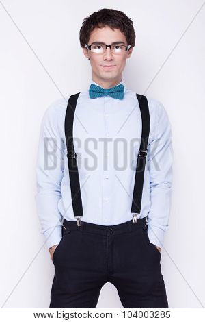 Handsome cheerful young man wearing glasses,  shirt with suspenders and a butterfly on his neck. Emo