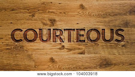 The word Courteous Engraved in Wooden Background