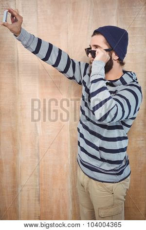 Side view of hipster with hooded shirt taking selfie while holding sunnglasses