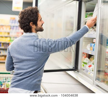 Man taking deep frozen food from a freezer in a supermarket
