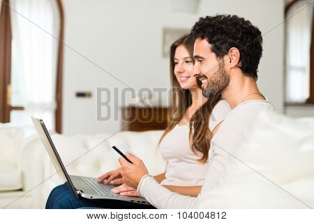 Happy couple shopping online, the man is holding a credit card