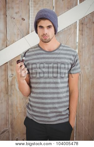 Portrait of man holding smoking pipe while standing against wooden wall