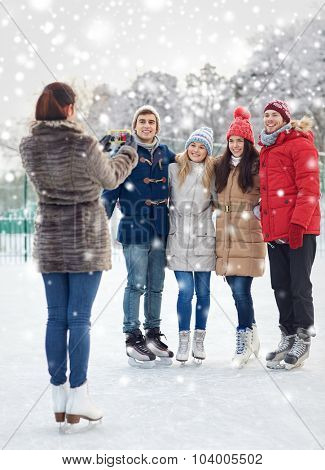 people, friendship, technology and leisure concept - happy friends taking picture with smartphone on ice skating rink outdoors