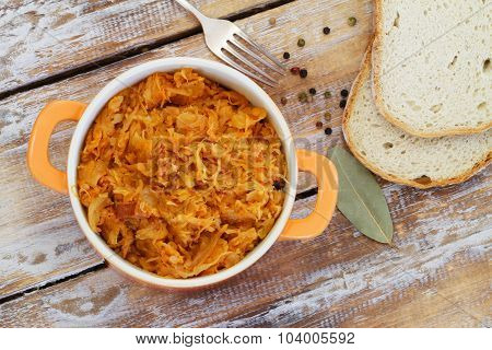 Polish bigos in saucepan on rustic wooden surface