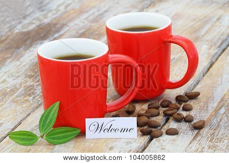 Welcome card with two mugs of coffee on rustic wooden surface