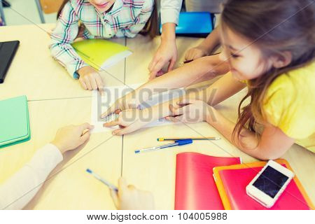 education, elementary school, learning and people concept - close up of school kids pointing fingers to paper with test on desk at classroom