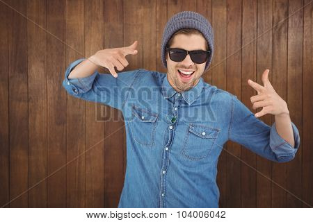 Happy hipster showing rock and roll hand sign against wooden wall