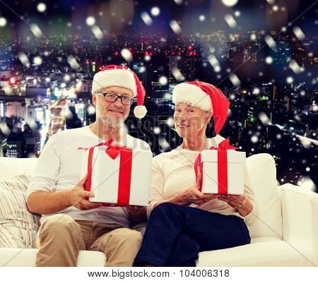 family, holidays, christmas, age and people concept - happy senior couple in santa helper hats with gift boxes over snowy night city background
