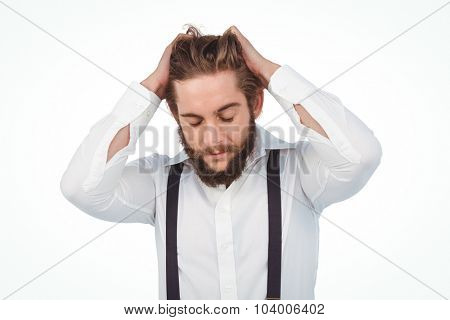 Frustrated hipster with head in hands against white backrground