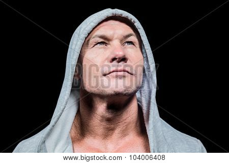 Athlete in hood looking up against black background