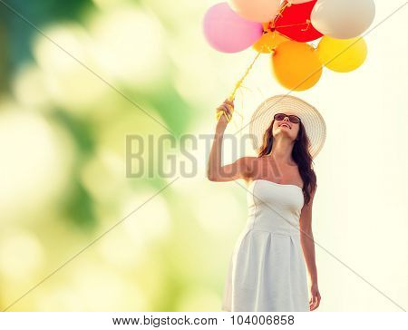 happiness, summer, holidays and people concept - smiling young woman wearing sunglasses with balloons over green background