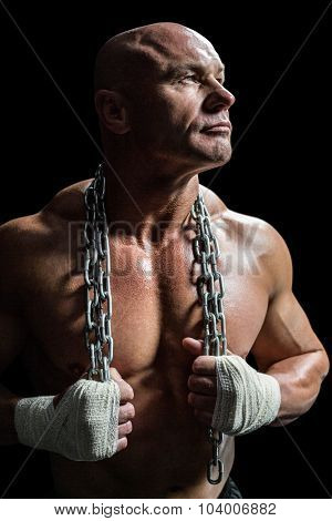 Muscular man holding chain while looking up against black background