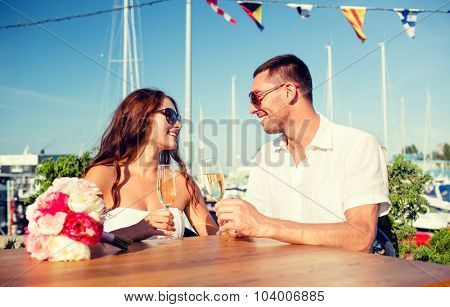 love, dating, people and holidays concept - smiling couple wearing sunglasses drinking champagne and looking to each other at cafe