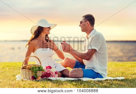 love, dating, people, proposal and holidays concept - smiling young man giving small red gift box with wedding ring to his girlfriend on picnic over seaside sunset background