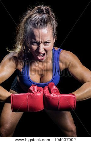 Portrait of aggressive female fighter flexing muscles against black background