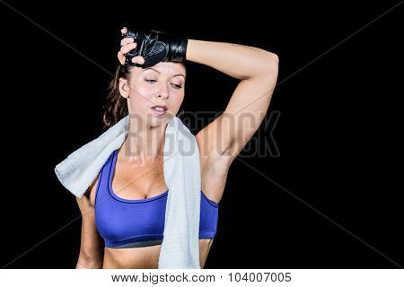 Tired athlete woman looking down against black background