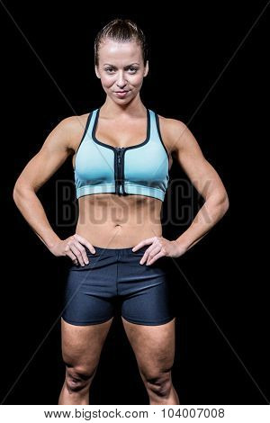 Portrait of beautiful fit woman with hands on hip against black background