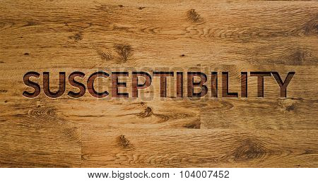 The word Susceptibility Engraved in Wooden Background