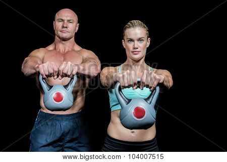 Portrait of muscular man and woman lifting kettlebells against black background