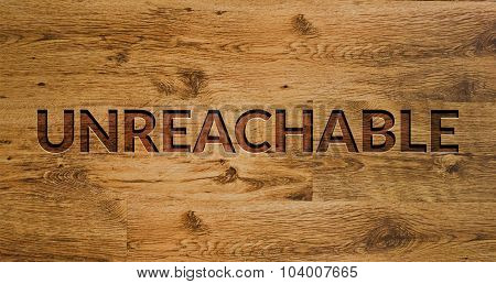 The word Unreachable Engraved in Wooden Background