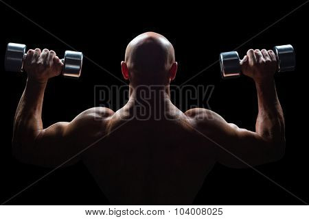 Rear view of muscular man lifting dumbbells against black background