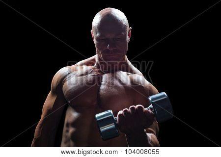 Concentrated bodybuilder lifting dumbbell against black background