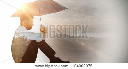 Businessman sitting on the floor with black umbrella against trees and mountain range against cloudy sky