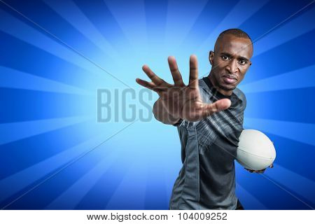 Close-up portrait of sportsman gesturing while standing with rugby ball against blue background