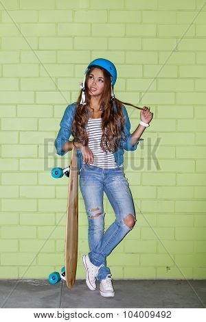 Beautiful Long-haired Girl With A Wooden Longboard Near A Green Brick Wall