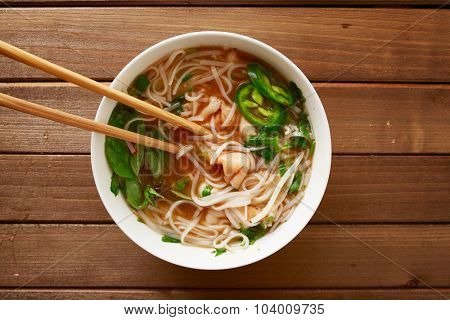 eating a bowl of vietnamese beef pho with chopsticks shot top down